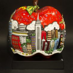 View of the left side of a porcelain apple sculpture featuring New York cityscape