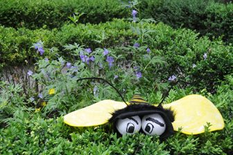 A felt bee with baseballs for eye perched on top of a green hedge with purple flowers in the background