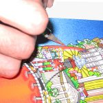 hand with exactoknife cutting a 3d pop art print - hand holding an pop art print of the new york city skyline in the shape of a red apple and a nyc subway train going through it like a worm, floating on an island next to the statue of liberty- 3D Pop Artist Charles Fazzino